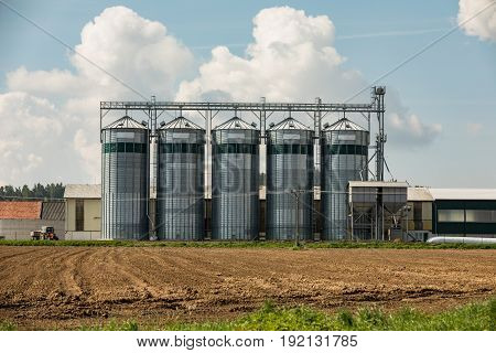Silos on the field. Grain Storage Bins. Elevator to store grain in a field on farmland.