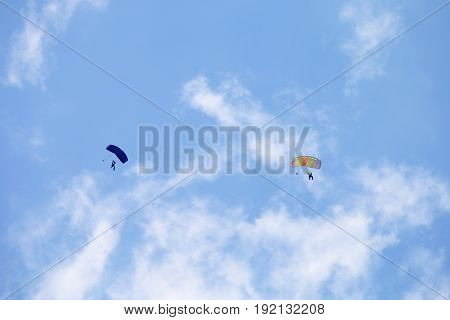 Two Skydivers With Colourful Chutes Circling In Queue For Landing.