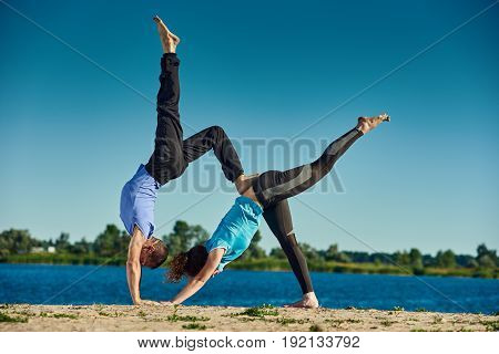 Man and woman practicing pair yoga poses outdoors