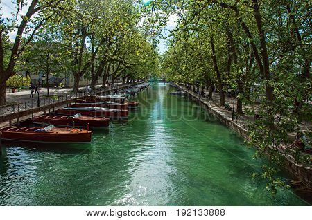 Large canal with boats and trees in the city center of historic Annecy. Located in the Haute-Savoie department, south-eastern France.