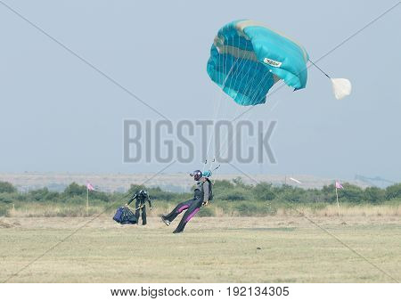 Black African Male Skydiver Making Safe Landing On Grass With Open Brightly Colourful Parachute.