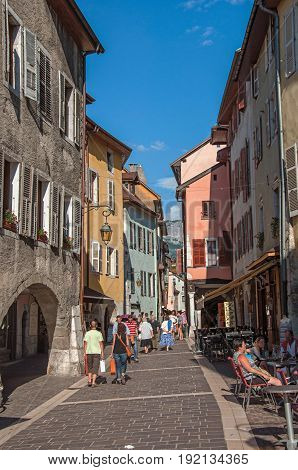 Annecy, France - June 30, 2016. Street with colorful old buildings and pedestrians, in the city center of historic Annecy, Haute-Savoie department, Auvergne-Rhône-Alpes region, south-eastern France