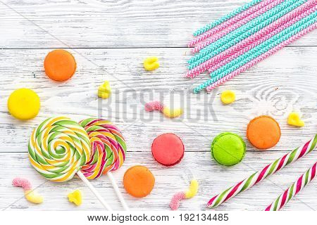 Sweets for birthday including lollipop and macarons on wooden desk top view copyspace.
