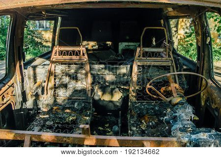Burned out car, inside view, rusty steering wheel and seats