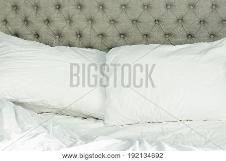 Unmade white bed with tufted linen headboard. Copy space.