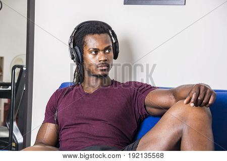Handsome black muscular bodybuilder man listening to music with headphones while sitting on couch