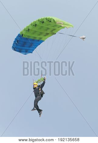Male Sky Diver With Brightly Coloured Open Parachute Gliding In Air