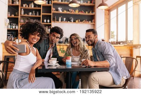 Young men and women sitting at cafe table and taking a self portrait on mobile phone. Diverse group of friends taking selfie on smart phone.