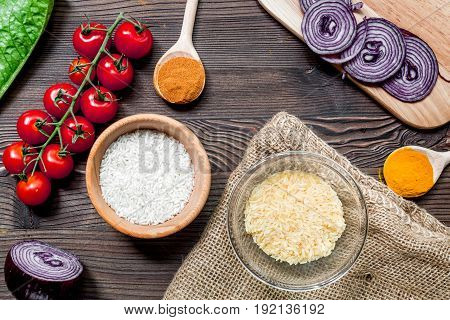 rice, spices and vegetables for paella on wooden kitchen desk background top view