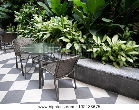 Table and Chairs in the Corner with Background of Tropical Green Plant.