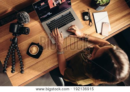 Young Female Vlogger Editing Her Vlog On Computer.