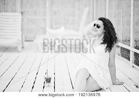 Portrait Of A Fabulous Young Woman In Sunglasses And Dress Sitting On White Wooden Floor With Her Dr