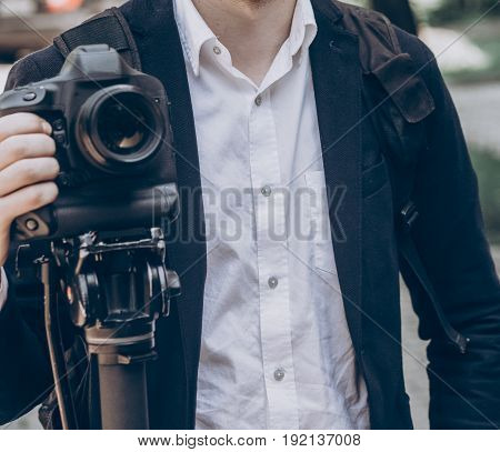 stylish man holding photo camera. professional holding video camera at wedding ceremony photographer or videohgrapher at celebration saving moments.