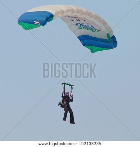 Female Sky Diver With Brightly Coloured Open Parachute Gliding In Air