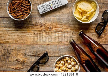 cinema and TV whatching with beer, crumbs, chips and pop corn on wooden background top view mock-up