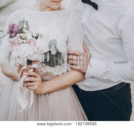 Stylish Wedding Bride And Groom Hugging In Sunny Park. Modern Couple Holding Fashionable Bouquet In
