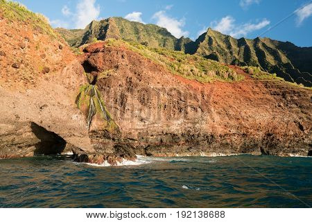 Sea arch and waterfall on Na Pali coastline in Kauai from sunset cruise