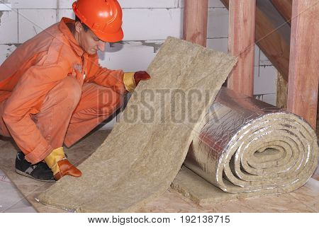 worker cuts off a strip of mineral wool