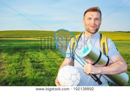 Beauty young man on a picnic with a backpack and rackets for a badbotton and a ball smiling against a green meadow. Camping, actively spending time outdoors