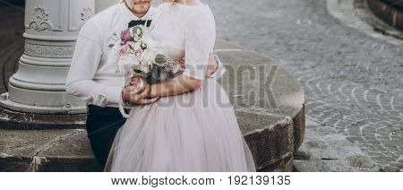 Stylish Wedding Couple With Bouquet. Modern Bride And Groom Holding Fashionable Bouquet At Old Stair