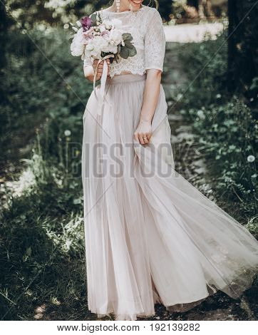 Stylish Wedding Bride With Bouquet And Amazing Modern Dress. Bride Posing And Smiling In Sunny Garde