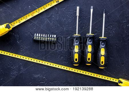 Tools for repairing on black stone table background top view.