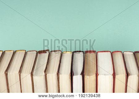 Colorful books on the table against the background of green wall. Copy space for text