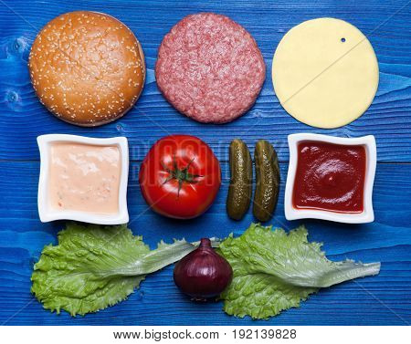 Ingredients for hamburger on blue wooden table.