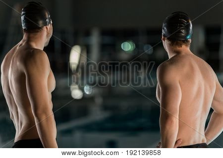 Rear view of two male swimmers with their hands on hips