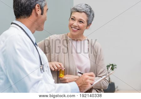 Senior doctor in conversation with senior woman holding medicine box. General practitioner and patient discussing at office. Happy doctor discussing with patient and prescribes pills.