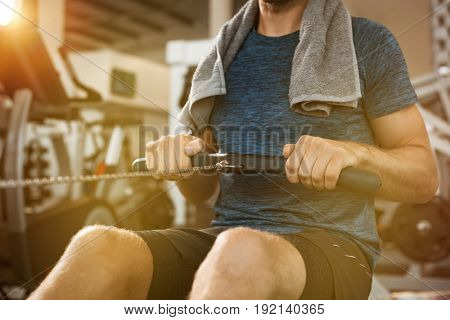 Young man working out with row machine at gym. Athletic man using rowing machine in the gym. Close up hand of fit man training at gym.