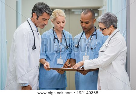 Group of senior doctors and young nurses examining medical report of patient. Team of doctors working together on patients file at hospital. Medical staff analyzing and working at clinic.