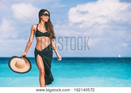 Luxury travel beach vacation elegant swimwear bikini woman with sunglasses, sun hat, black pareo. Body skin care lifestyle.