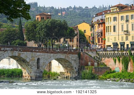 Verona, Italy - June, 16, 2017: embankment of Adige river in Florence, Italy with Ponte Pietra bridge
