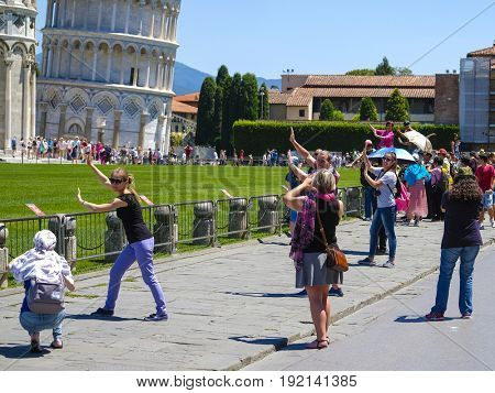 Pisa, Italy - June, 15, 2017: tourists try to be photographed against the background of the well-known falling tower in Pisa, Italy so that it seemed that they support tower