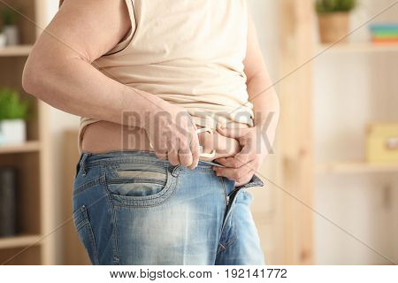 Fat man with measuring caliper at home, closeup. Weight loss concept