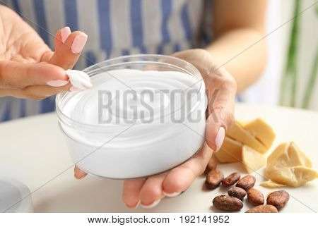 Woman holding jar with cocoa butter lotion over table