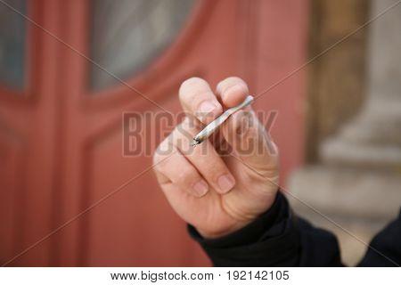 Man smoking weed on blurred background