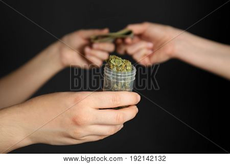 Woman buying weed buds in container on black background