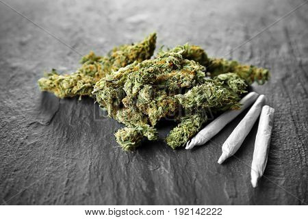Heap of weed buds and cigarettes on dark background