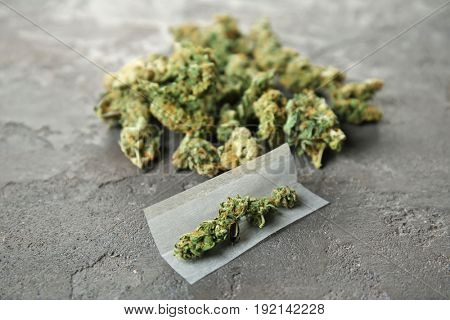 Weed buds and cigarette paper on grey background