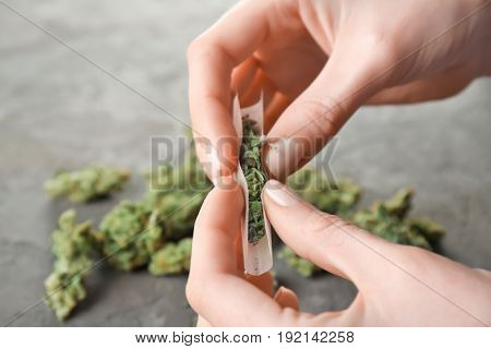 Woman making cigarette with weed bud, closeup