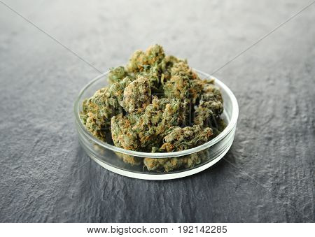 Heap of weed buds in Petri dish on grey background