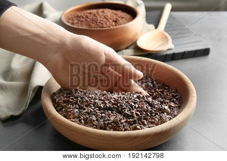 Human hand taking pile of cocoa nibs from wooden bowl