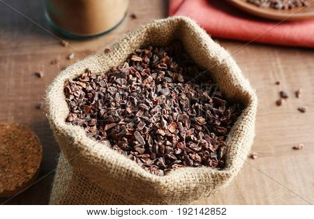 Bag with cocoa nibs on wooden table