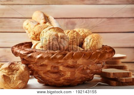Baked basket with fresh bread on wooden background