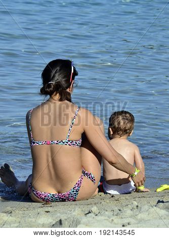 Baby and mother enjoy the beach and sea.