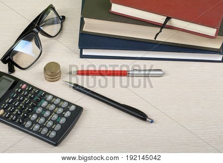 Home savings, budget concept. Notepad, calculator, pencil, eyeglasses and coins on wooden office table