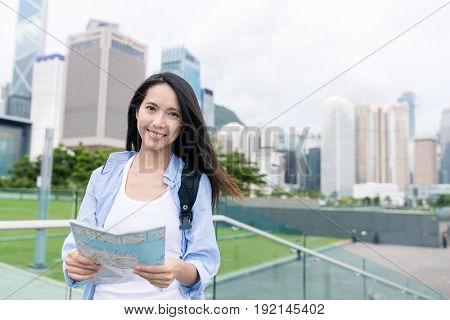 Woman use of city map in Hong Kong cityscape