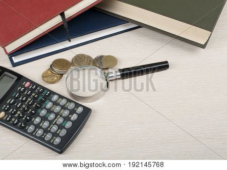 Home savings, budget concept. Notepad, calculator and magnifying glass on wooden table